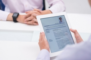 Close-up image of employer reading cv of job candidate